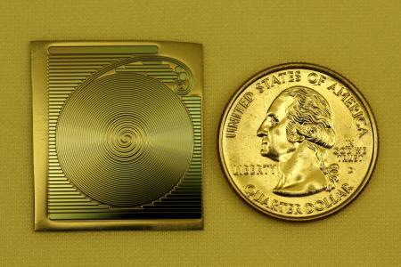 A photograph of the spiral chip-based optical resonator developed at Caltech, shown next to a quarter to provide scale. (Source: Caltech) A miniaturized optical oscillator would represent a shift in the traditional roles of photonics and electronics. Currently, electronics perform signal processing while photonics rule in transporting information from one place to another over fiber-optic cable. Eventually, oscillators in high-performance electronics systems, while outwardly appearing to be electronic devices, will internally be purely optical.