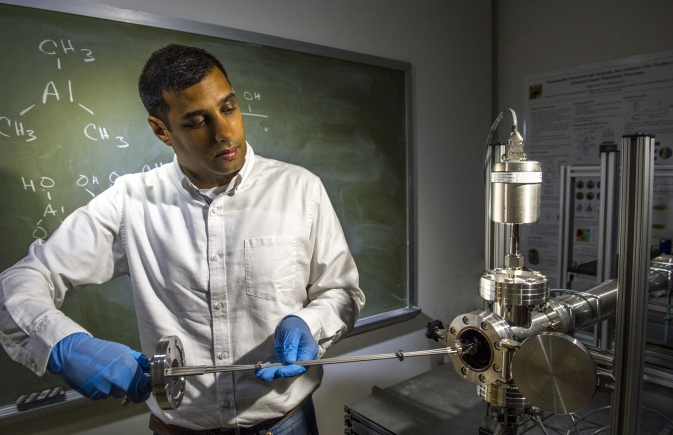 "NASA technologist Vivek Dwivedi, who has distinguished himself as the go-to-engineer for atomic layer deposition, has assembled a new reactor at NASA's Goddard Space Flight Center that he plans to use for thin-film experimentation. He is inserting one of his ""virtual toothpick"" technologies. Image Credit: NASA Goddard/Bill Hrybyk"