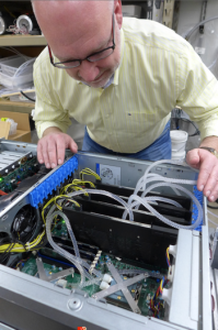 Timothy Shedd examines a computer equipped with his novel cooling system. Tubes circulate refrigerating fluid through a special heat exchanger (under the X-shaped structure) on the processor that is the biggest heat source in a computer. (Photo source: David Tenenbaum/UW-Madison)