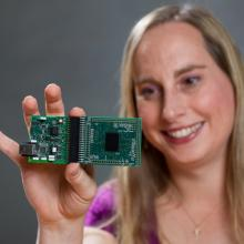 Georgia Tech professor Jennifer Hasler displays a field programmable analog array (FPAA) board that includes an integrated circuit with biological-based neuron structures for power-efficient calculation. Hasler's research indicates that this type of board, which is programmable but has low power requirements, could play an important role in advancing neuromorphic computing. (Source: Georgia Tech)