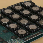 A circuit board shows 16 of the new brain-inspired chips in a 4 X 4 array along with interface hardware. (Source: DARPA/IBM)