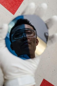 Ke Sun, a Caltech postdoc in the lab of George L. Argyros Professor and Professor of Chemistry Nate Lewis, peers into a sample of a new, protective film that he has helped develop to aid in the process of harnessing sunlight to generate fuels. (Source: Lance Hayashida/Caltech Marcomm)