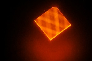"In this image, laser light enters a synthetic diamond from a facet at its corner and bounces around inside the diamond until its energy is exhausted. This excites ""nitrogen vacancies"" that can be used to measure magnetic fields. (Source: MIT)"