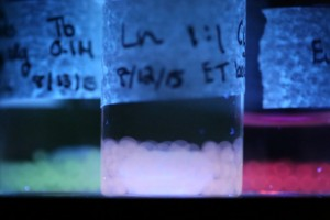Luminescent materials produced by the MIT team are shown under ultraviolet light, emitting different colors of light that can be modified by their environmental conditions. These light-emitting beads were made by materials science and engineering students Caroline Liu and Rebecca Gallivan. (Source: MIT)