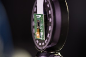 Rice University's FlatCam – the tiny chip attached to the circuit board — is a lens-less camera that may someday turn large or small surfaces into cameras. (Source: Rice University)