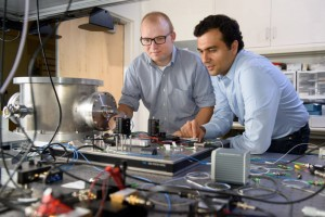Post-doctoral scholar Peter McMahon, left, and visiting researcher Alireza Marandi examine a prototype of a new type of light-based computer. (Source: Stanford University)
